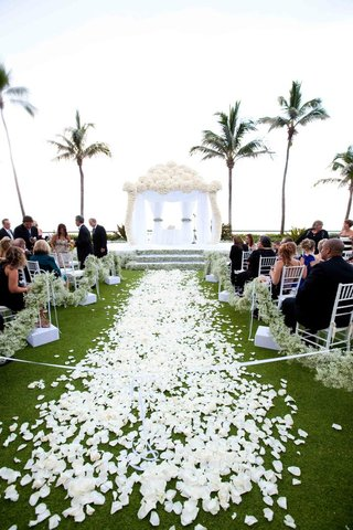 white-flower-petals-on-grass-aisle-lead-to-white-flower-chuppah