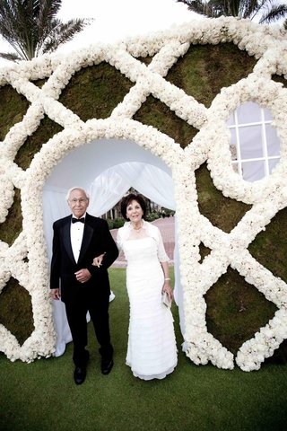 father-and-mother-of-groom-in-front-of-flower-wall