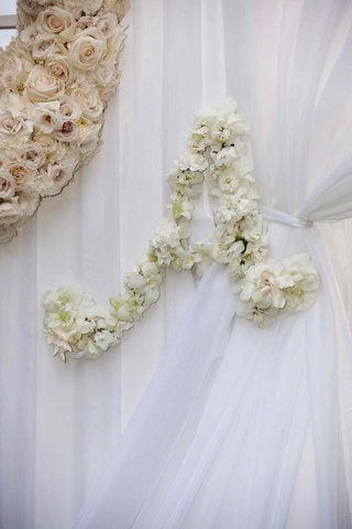 white-ceremony-drapes-tied-with-flower-initial