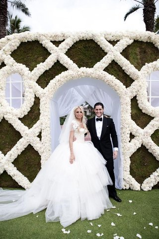 bride-in-full-tulle-skirt-and-groom-in-front-of-rose-wall