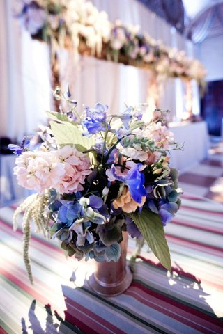 pink-purple-and-blue-flowers-in-metallic-vase-on-striped-table