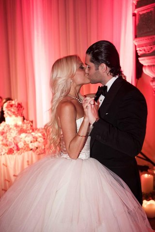 bride-and-groom-kiss-at-pink-wedding-reception