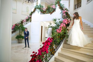 bride-in-strapless-wedding-dress-long-hair-walking-down-staircase-foyer-of-home