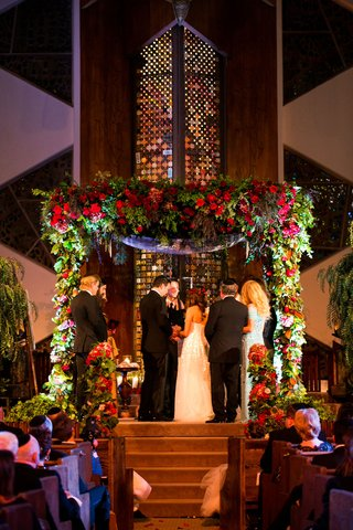bride-and-groom-under-chuppah-with-greenery-and-red-flowers-indoor-jewish-temple-wedding-ceremony
