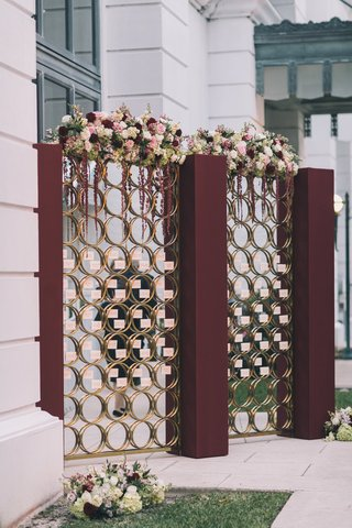 burgundy-pillars-with-glass-pane-gold-rings-escort-cards-florals-on-top