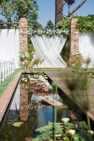 wedding-ceremony-belmond-el-encanto-pond-flowers-lilies-along-aisle-white-drapery-flowers