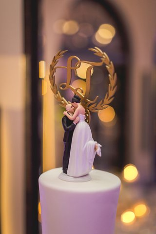wedding-cake-topper-with-bride-popping-foot-and-kissing-groom-monogram-in-gold-cake-topper