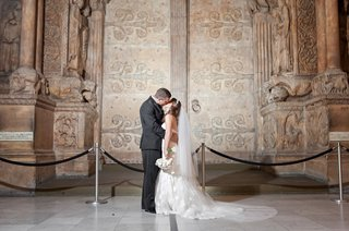 bride-and-groom-next-to-ancient-door-on-display