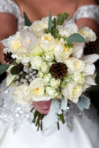 bride-carrying-pinecones-leaves-and-white-flowers