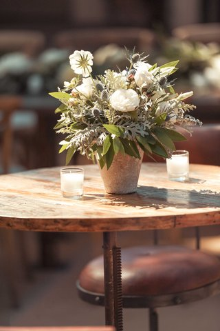 rustic-round-wood-cocktail-table-outdoor-wedding-reception-candles-white-flower-greenery-centerpiece