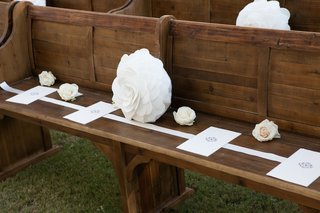 white-programs-and-roses-on-wood-church-pew-at-outdoor-wedding
