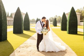bride-in-ines-di-santo-mermaid-wedding-dress-with-ruffles-groom-in-white-tuxedo-jacket