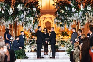 same-sex-wedding-inspiration-two-grooms-exchanging-vows-at-vibiana-large-floral-display