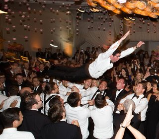 groom-without-tuxedo-jacket-body-surfing-crowd-surfing-at-wedding-reception-during-hora-jewish