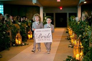 wedding-ceremony-at-church-lanterns-and-greenery-along-aisle-white-aisle-runner-grey-ring-bearer