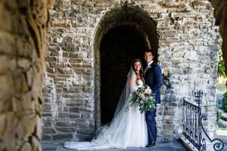 bride-in-strapless-wedding-dress-with-veil-hair-down-groom-with-navy-blue-suit-and-burgundy-bow-tie