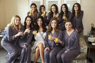 bride-in-white-robe-bridesmaids-in-dusty-purple-pajama-sets-mimosas-while-getting-ready