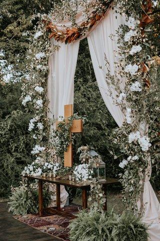 wedding-ceremony-vintage-rug-wood-table-altar-cross-magnolia-greenery-burgundy-flowers