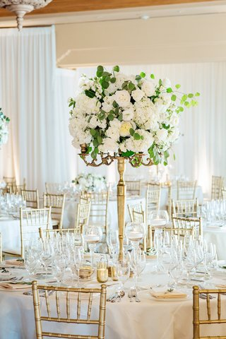 white-roses-and-eucalyptus-leaves-on-thin-gold-stand