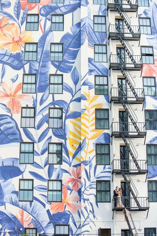 wedding-portrait-in-downtown-los-angeles-on-fire-escape-of-building-tropical-flower-leaf-mural