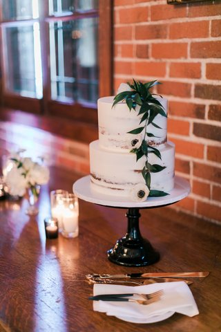 wedding-cake-on-cake-stand-with-two-layer-wedding-cake-semi-naked-confection-greenery-anemone-flower