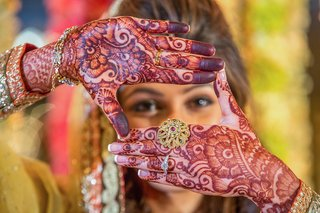 bride-looking-through-henna-hands-with-intricate-ring