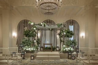 grey-wooden-chuppah-with-accents-of-greenery-at-indoor-wedding
