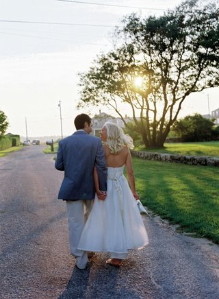 bride-and-groom-walk-towards-sunset-on-private-estate