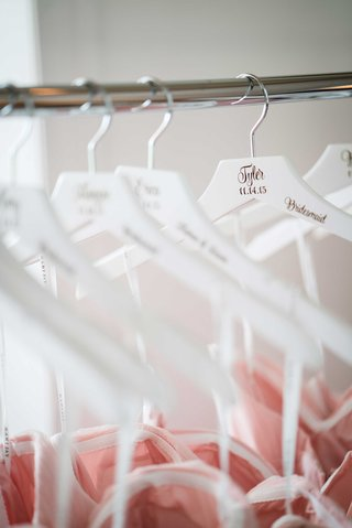 personalized-white-bridesmaid-hanger-with-blush-dresses-wedding-date-name-and-wedding-title