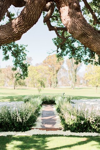 ojai-valley-inn-wedding-ceremony-with-aisle-lined-by-greenery-and-flowers