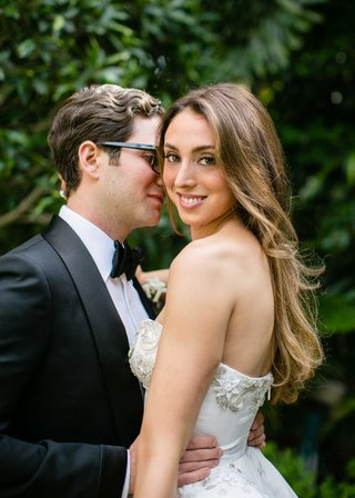 groom-in-tom-ford-tuxedo-bow-tie-glasses-holds-bride-in-strapless-oscar-de-la-renta-wedding-dress