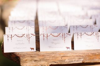 minted-wedding-escort-cards-with-confetti-circle-motif-animal-stamps-for-entree-table-numbers-wood