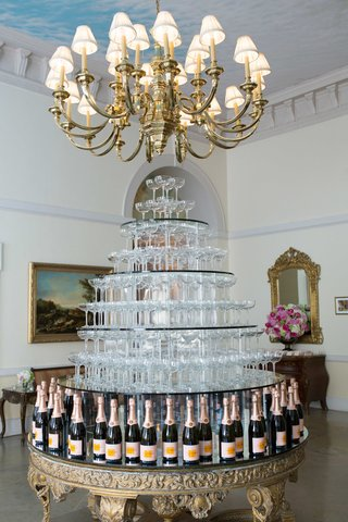 gold-ornate-table-with-champagne-bottles-holding-up-tiers-of-coupe-champagne-glasses-in-tower