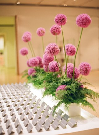 pink-allium-flowers-in-planter-with-ferns-in-front-at-modern-museum-escort-card-table
