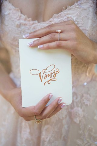 bride-with-engagement-ring-and-french-manicure-holding-vows-book-white-book-gold-calligraphy