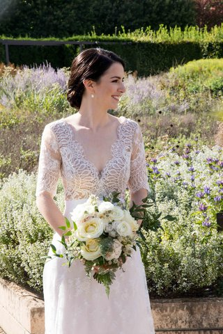 bride-in-lace-v-neck-carolina-herrera-gown-holds-ivory-bouquet-with-greenery