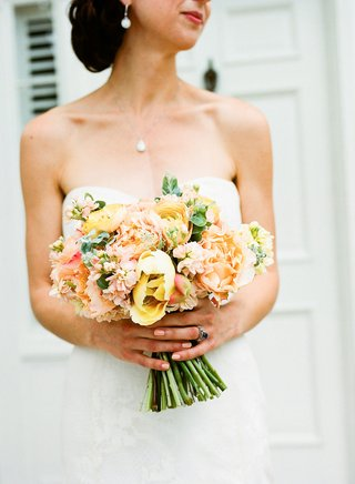 spring-wedding-ideas-bright-peach-yellow-pink-orange-wedding-bouquet-bride-holding-stems-greenery