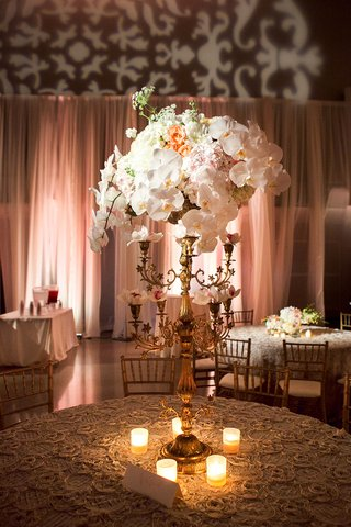 wedding-reception-centerpiece-of-golden-candelabra-with-white-orchids-orange-roses-and-hydrangeas