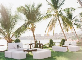 wedding-cocktail-hour-reception-grass-lawn-white-seating-lounge-areas-wood-tables-minimal