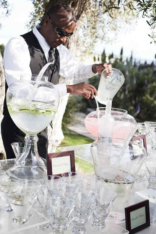 african-american-server-pours-pitcher-into-water-urn