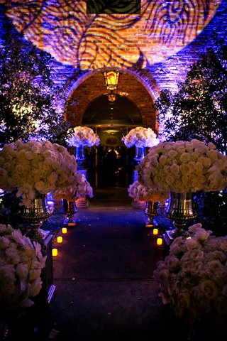 purple-lighting-outside-wedding-venue-with-lush-white-rose-flower-arrangements-leading-to-room