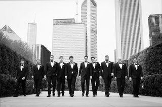 black-and-white-photo-of-groom-and-groomsmen-walking-through-city-of-chicago