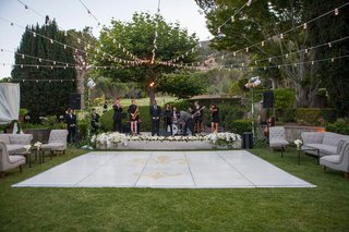 white-outdoor-dance-floor-couples-gold-logo-strings-of-lights-lounge-furniture-stage-live-band