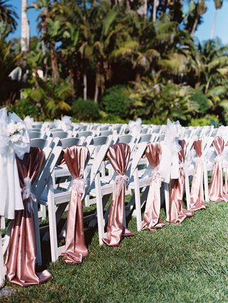 white-wedding-ceremony-chairs-on-grass-lawn-with-pink-silk-satin-linens-tied-with-ribbon-chair-cover
