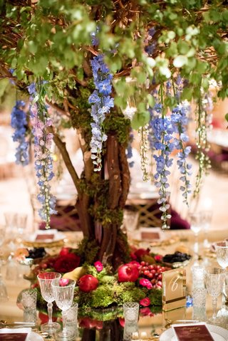 wedding-reception-centerpiece-tall-tree-cascading-flowers-moss-and-fruit-at-base-grape-pomegranate