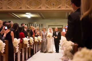 bride-in-a-lace-monique-lhuillier-gown-is-walked-down-the-aisle-by-her-parents