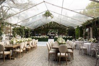 wedding-reception-under-clear-top-tent-wood-floor-greenery-hedge-wall-neutral-decor