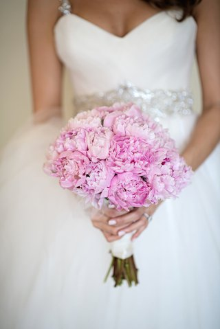 bride-holding-garden-roses-or-peonies-wrapped-in-white