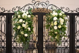 black-gate-with-white-flowers-and-greenery-to-serve-as-backdrop-of-ceremony