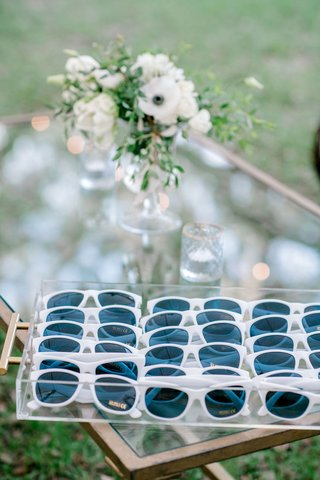 wedding-guest-favors-outdoor-ceremony-white-sunglasses-on-coffee-table-white-flower-centerpiece